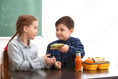 Obraz Little boy sharing his school lunch with girl in classroom - fototapety do salonu