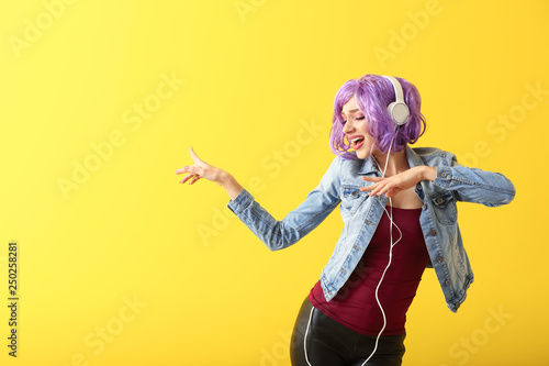 Fototapeten Tanzschule Beautiful young woman with headphones dancing against color background