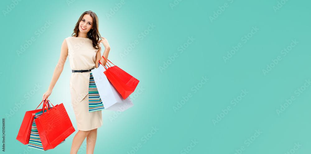 Fototapeta Beautiful woman with shopping bags, over blue