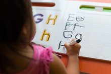 Kid Learning How To Write The Abc's At Home.