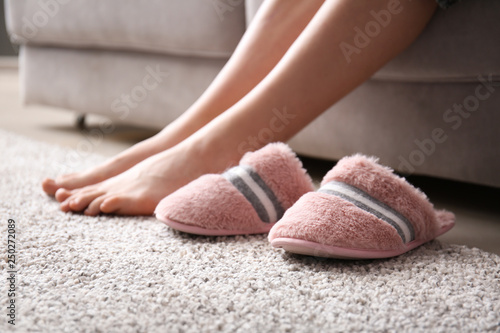 Fotografía Legs of barefoot woman near soft slippers on carpet