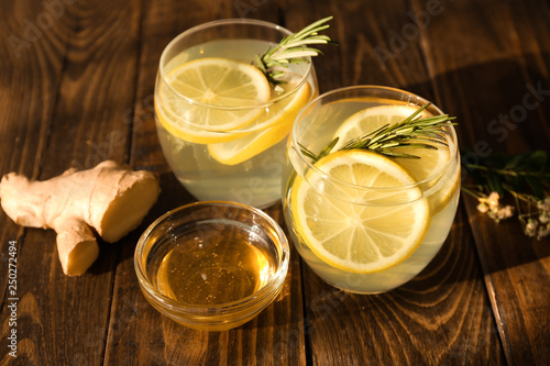 Fototapeta Glasses of fresh lemonade, honey and ginger on wooden table obraz