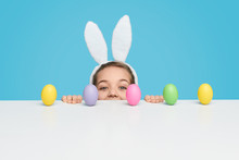 Girl With Peeking Out From Behind Table With Easter Eggs