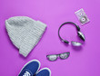 Leinwanddruck Bild - Pop culture attributes from the 80s on a purple paper surface. Headphones, audio cassette, sneakers, hat, 3D glasses