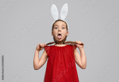 Fototapeta  Funny girl in bunny ears choking with braids