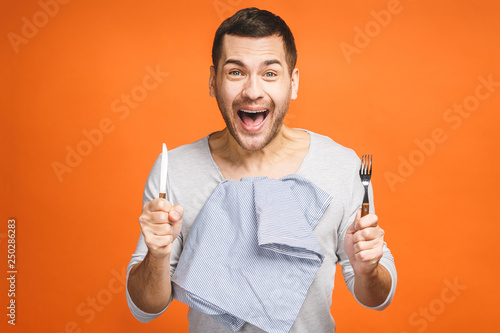 Fotomural Young hungry crazy man holding a fork and a knife