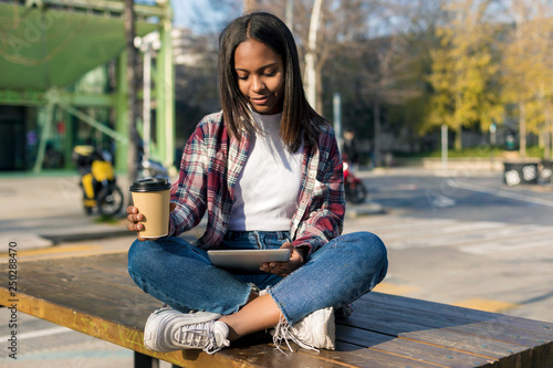 obraz PCV Young beautiful african american woman sitting outdoors in the city with a tablet pc while holding a take away coffee in a sunny day