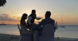 Bride and Groom Eat Together on Beach after Wedding, Sunset