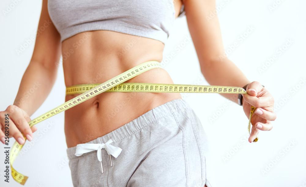 Fototapety, obrazy: Crop slender woman measuring waist line