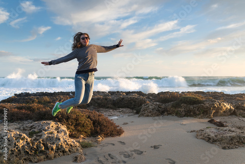 Foto auf AluDibond Grau girl jumping on the beach at sunset