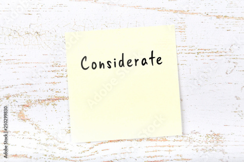 Photo  Yellow sticky note with handwritten word considerate