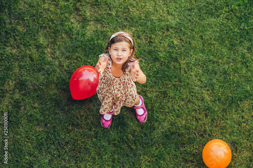 Happy little girl playing with colorful balloons outdoors, top view фототапет