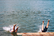 Men Jumping Off Wooden Pier, Feet Splashing On Entry To Water