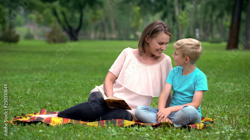 Son and mother reading interesting adventure book, sitting on blanket in park Wallpaper Mural