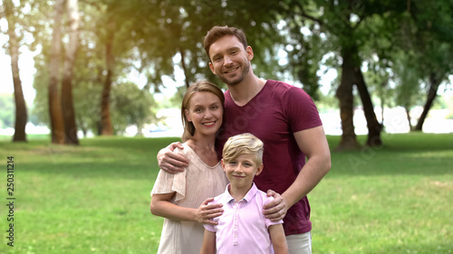 Fotobehang School de yoga Happy family embracing and looking at camera, social insurance, protection
