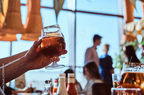 Young guy holding a glass of beer sitting in a caf with his friends