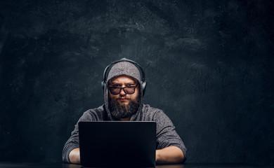 A hacker sits behind a lapt...