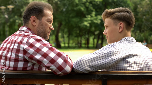 Serious son and dad talking on bench in park, father sharing life experience