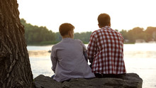 Male Teenager And His Father Sitting On Stone Near Lake And Talking About Life