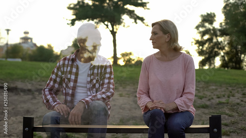 Fotografia  Depressed old woman sitting on bench, husband appearing beside, loss, memories