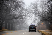 SUV Driving Over A Hill On City Street Under Spooky Bare Overhanging Branches During A Heavy Fog - Dead End Sign