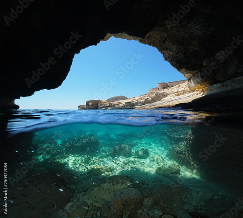 Inside a cave on the seashore, split view half over and under water, Mediterranean sea, Spain, Cabo de Gata Nijar natural park, Almeria, Andalusia