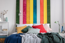Close-up Of A Colorful Bed With Cushions And Blankets Standing Against White Wall With Striped Painting In Bedroom Interior. Real Photo