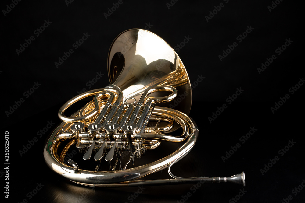 Fototapeta French horn on a wooden table. Beautiful polished musical instrument.