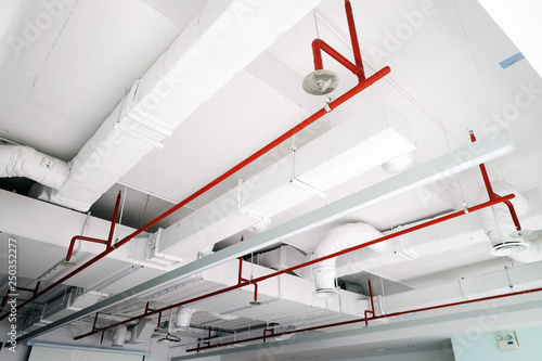 Obraz Perspective view of white air duct on the ceiling with red water sprinkler pipe - fototapety do salonu