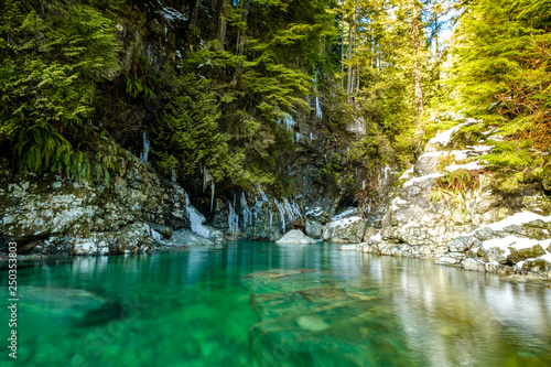 Fototapety, obrazy: clear see through green water flow over rocky creek by the cliff with rocks covered in ice and snow in a sunny winter day