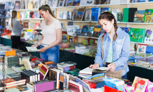 glad woman showing open book to attentive girl in book boutique Poster Mural XXL