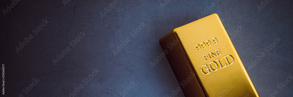 Fototapeta An ingot of gold metal bullion of pure brilliant diagonally located on a blue textured background.