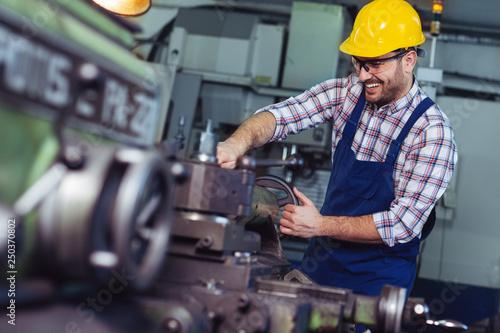 Fotografia  Worker in uniform operating in manual lathe in metal industry factory