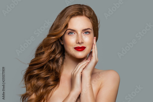 Fotografie, Obraz  Pretty woman with ginger curly on blue background