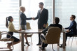 Happy middle-aged boss handshaking welcoming new partner at team meeting