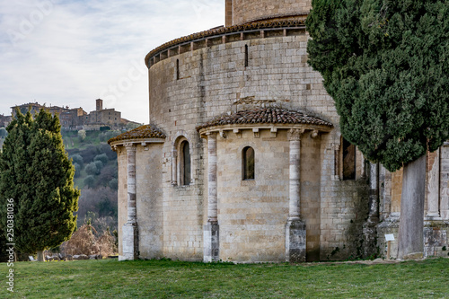 Foto  Detail of the apse of the Sant'Antimo Abbey with in the background the village o