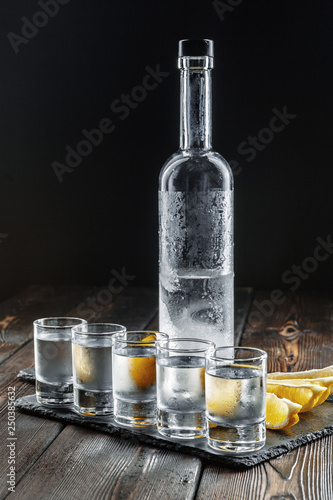 Photo Vodka in shot glasses on rustic wood background