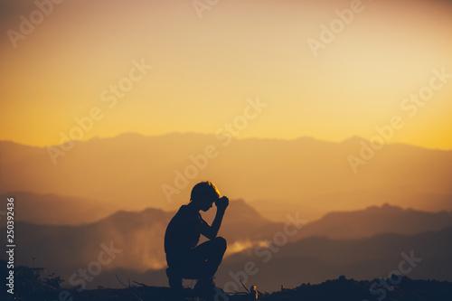 Fotografía  Man sitting praying and worshipping God at sunset background
