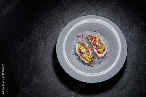 Photo  Fresh raw open oysters in crashed ice on black background