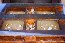 Clear Glass Table With Seashell Inside. Sand With Seashells In The Box