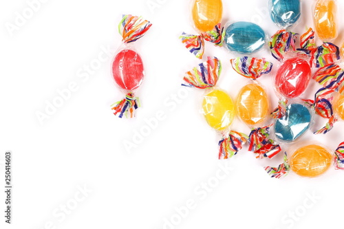 Fotografía  Colorful hard candies in transparent cellophane wrapping, isolated on white back