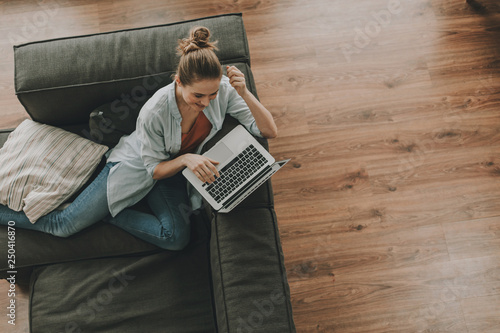 Relaxed female on sofa with laptop on back-rest
