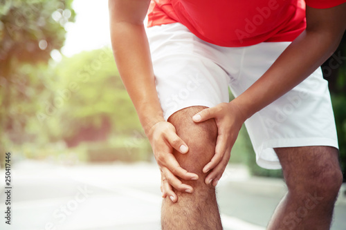 Runner touching painful twisted or broken ankle  Athlete