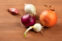 An Assortment Of Various Types Of Onions Of A Dark Rustic Wooden Background With A Place For Text