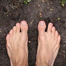 Barefoot Man Stands On Empty Black Soil Ground In Spring, Square Frame, Top View, Closeup