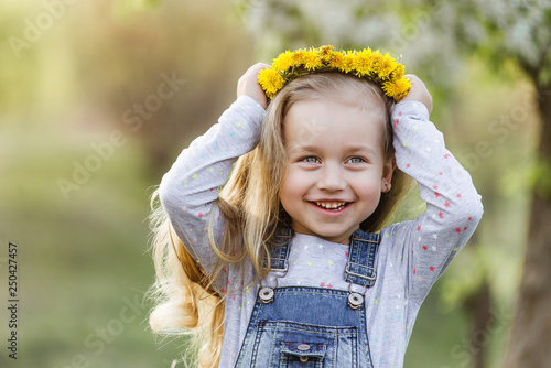 Photo  Spring sunny portrait of a cute 4 year old girl posing with a dandelion wreath,