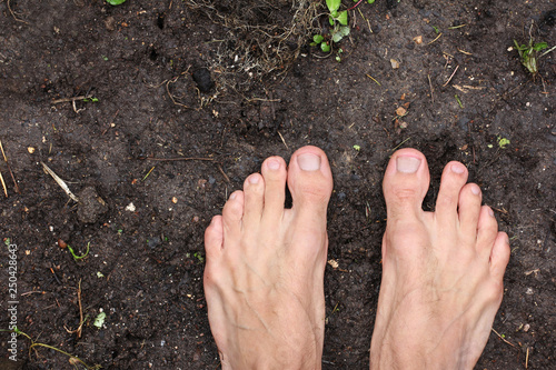 Photo barefoot man stands on empty black soil ground in spring, poster for ecology fit