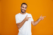 Image of smiling guy 30s in t-shirt pointing fingers aside while standing, isolated over yellow background