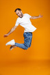 Full length photo of positive guy in t-shirt and jeans jumping and having fun, isolated over yellow background