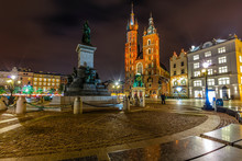 Adam Mickiewicz Monument On Main Market Square In Front Of  St. Mary's Basilica  In Krakow, Poland At Night
